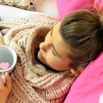girl in bed drinking tea against flu
